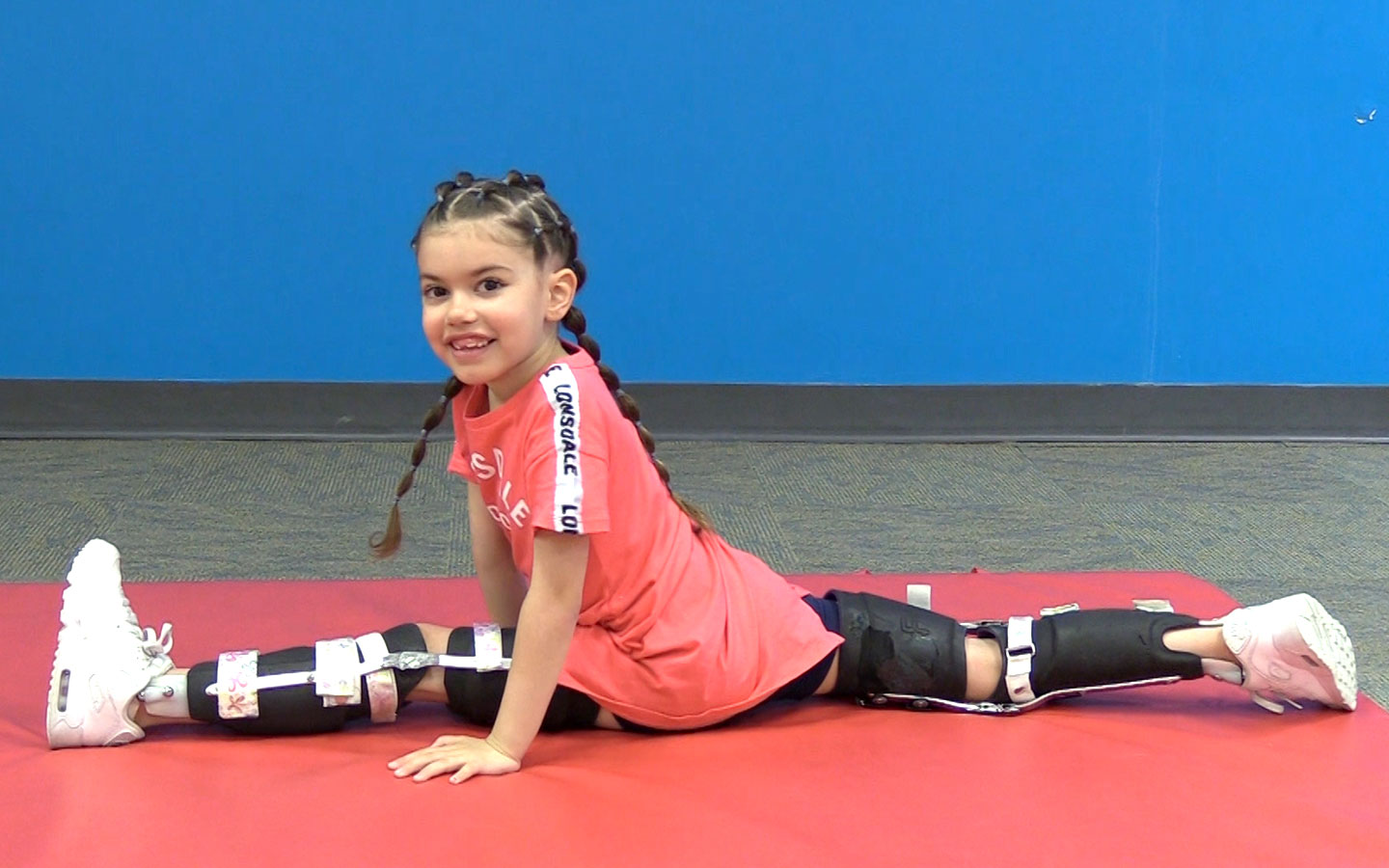 Novita Kid Tiffany wearing her leg braced and doing the splits.