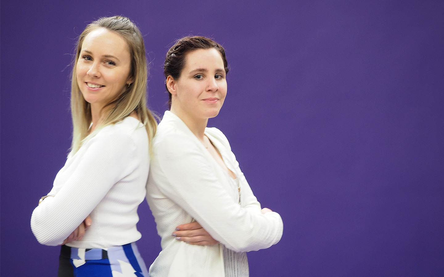 Two women standing in front of a purple background