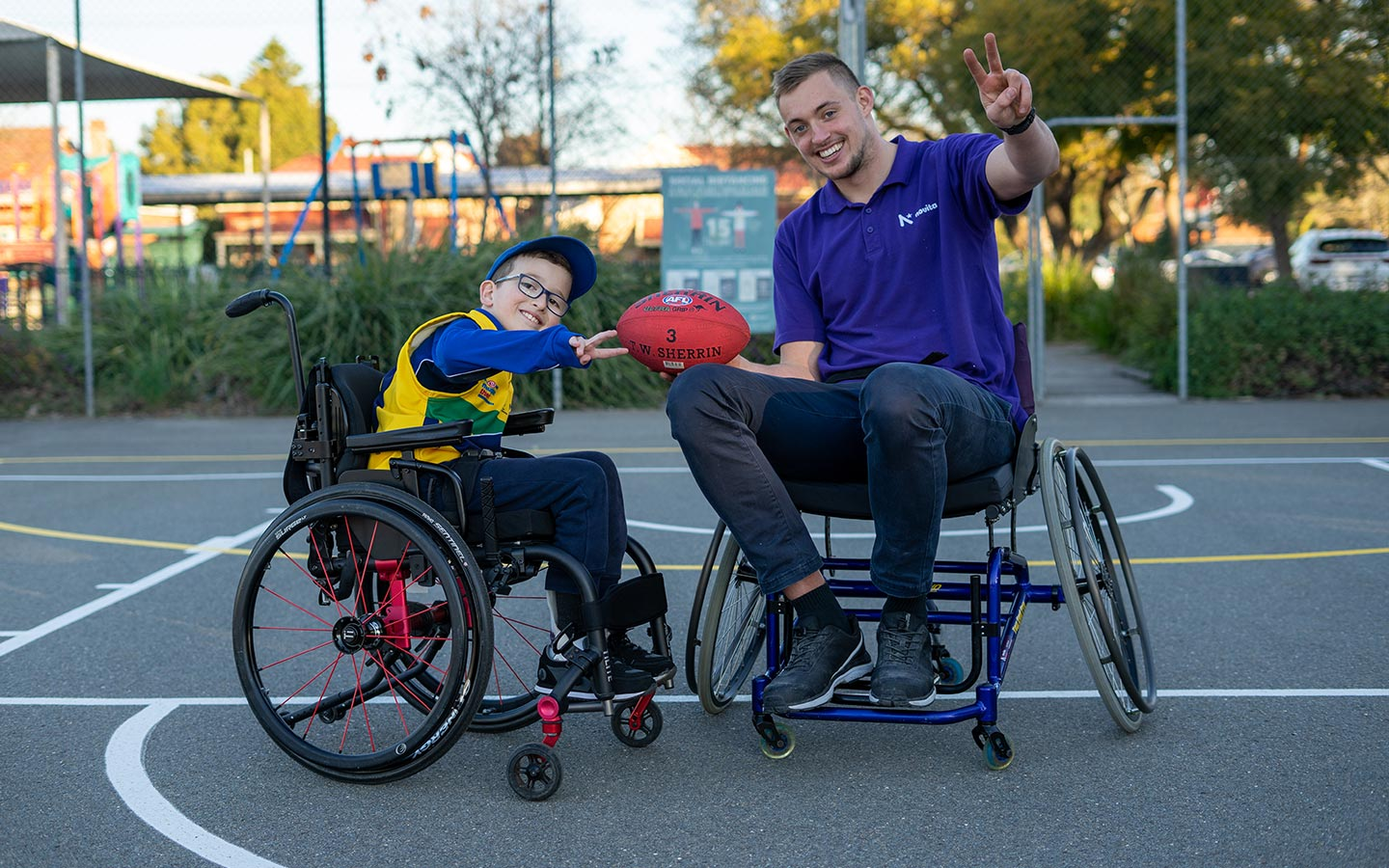 Young boy in a wheelchair and man in a wheelchair holding a football